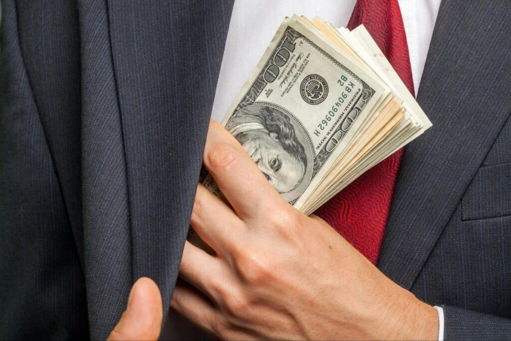 timeshare scams: person putting money into his suit jacket pocket