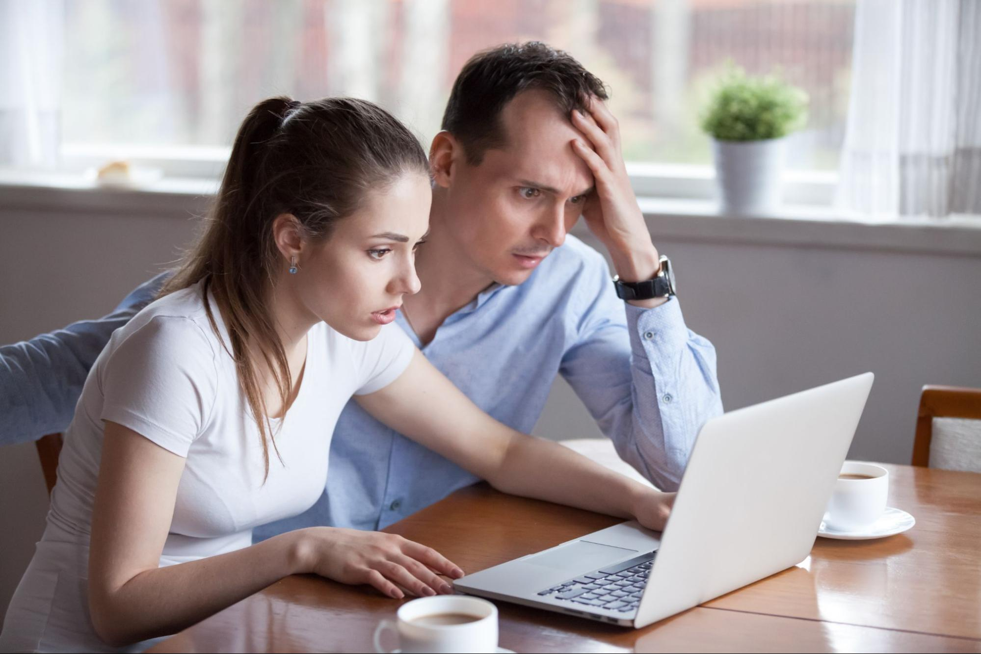 Worried couple looking at their laptop