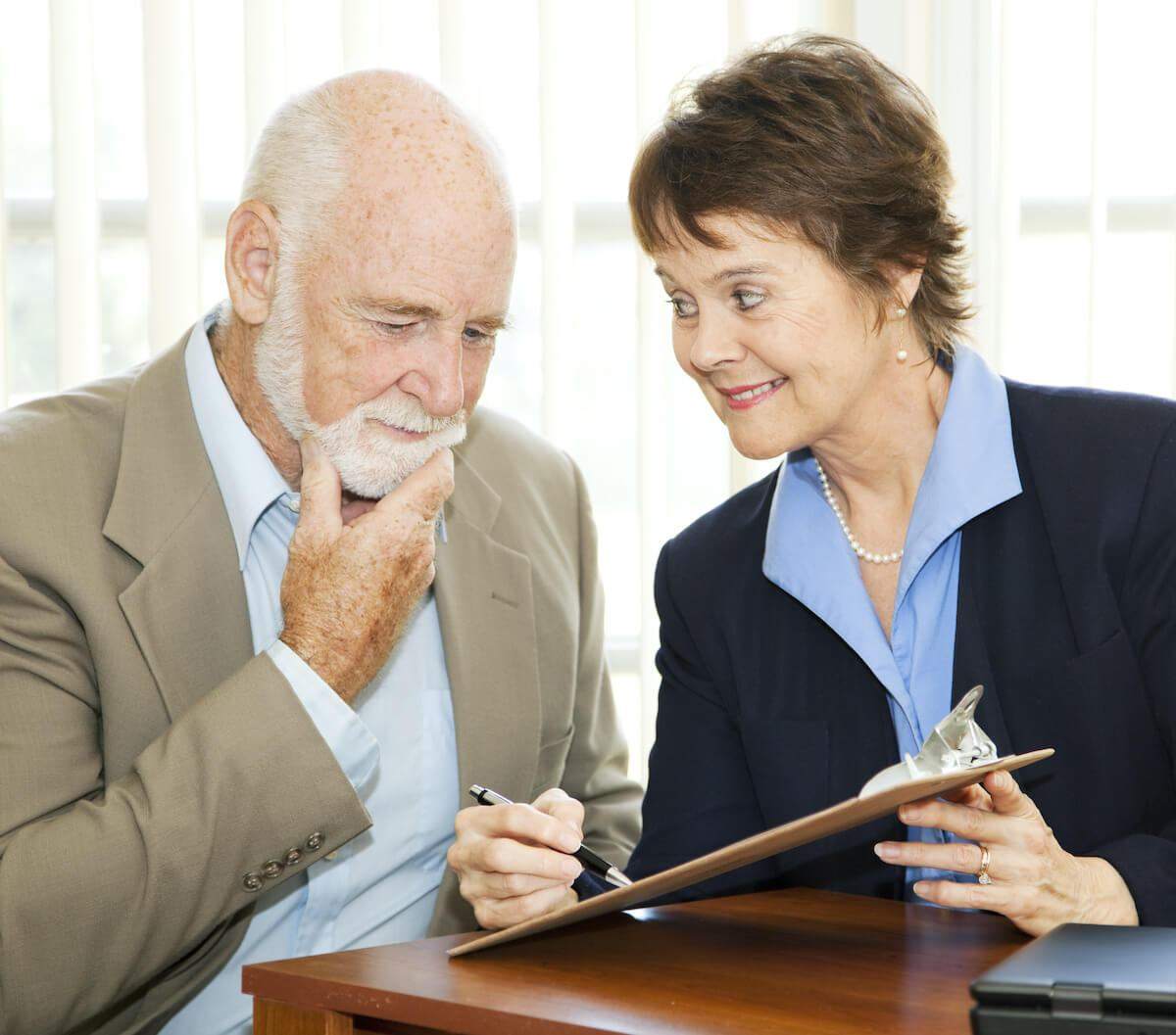 are timeshares scams: Elderly man thinking about signing a document while a woman looks at him