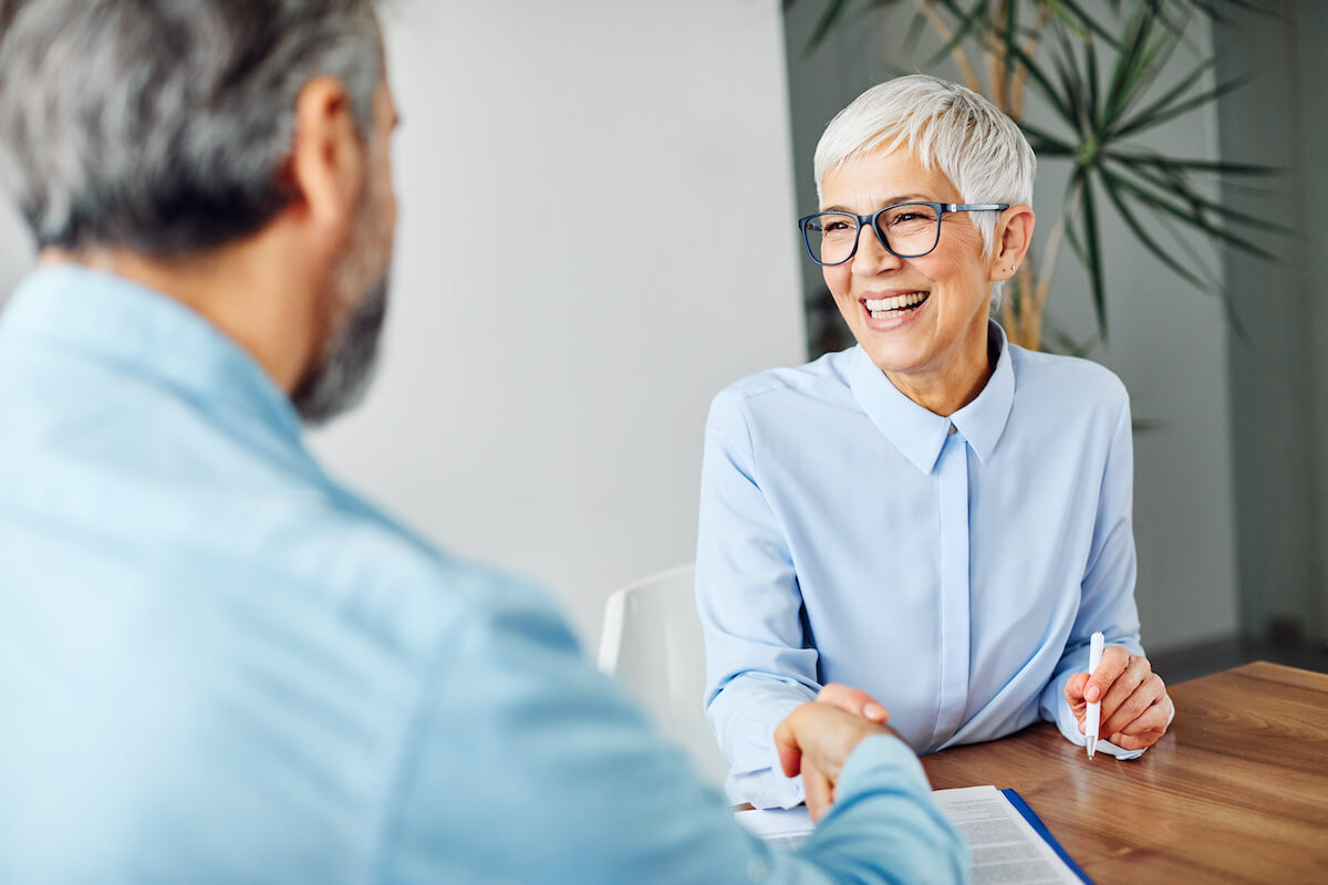 Smiling elderly woman shaking hands with a man