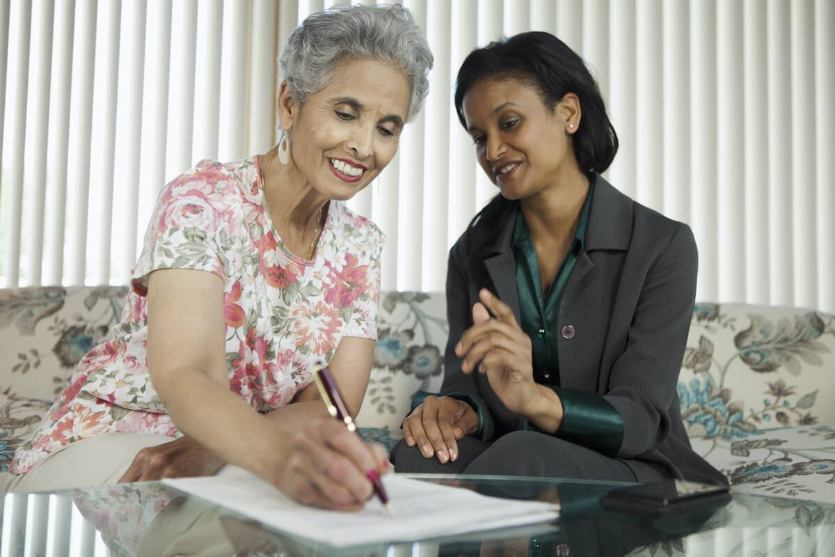 donating timeshares: Woman watching an elderly woman sign a document