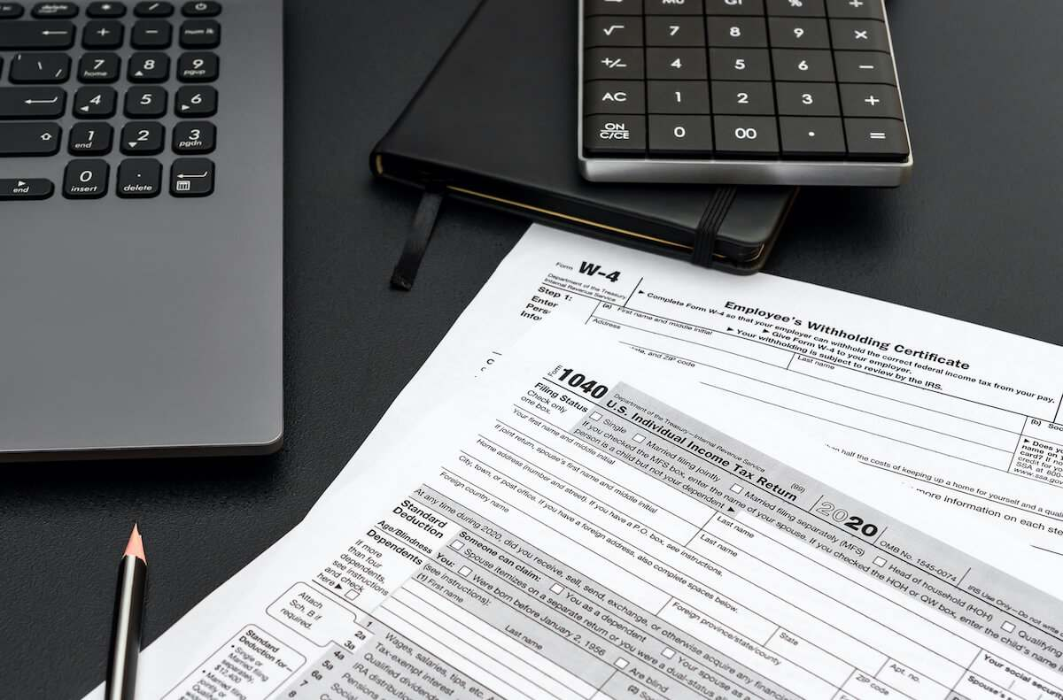 Tax forms, laptop, notebook and calculator on a black surface